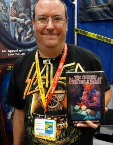Clad in a Slayer shirt, game designer Todd Breitenstein holds up The Current Number of the Beast at Comic-Con booth
