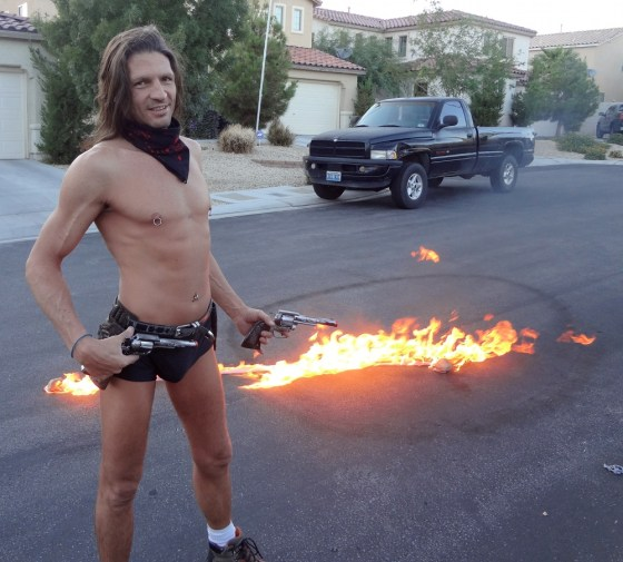 Shirtless and tan male burlesque dancer Kevin Matthews with pistol and fire on asphalt behind him