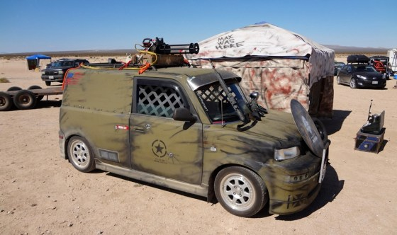 Scion coverted to military Wasteland Paint scheme with chain gun on roof at Wasteland Weekend
