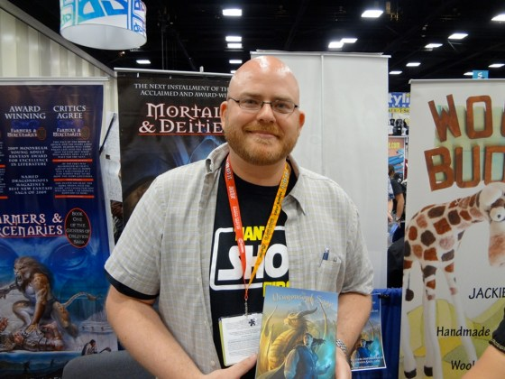 Fantasy Author J.T. Hartke holding his book A Balance Broken at his booth at Comic-Con in San Diego