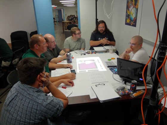 Pathfinder Society players listen attentively to GM with elaborate rig above projecting image of playing map