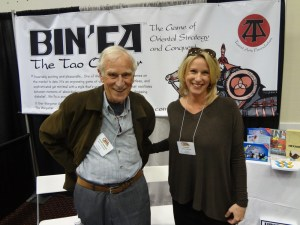 Game Designer Ken Hodkinson and daughter Erika Bird in front of Bin'fa poster at GAMA Trade Show