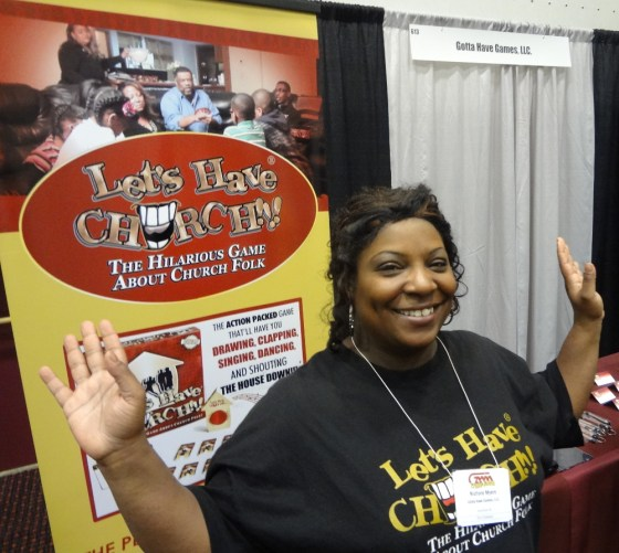 Game Designer Nichole Myers raising the roof for Let's Have Church at the GAMA Trade Show
