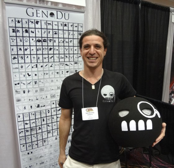 Eytan Benichay stands with Jack-in-the-box style Gen Dun head in front of poster displaying cards at GAMA Trade Show