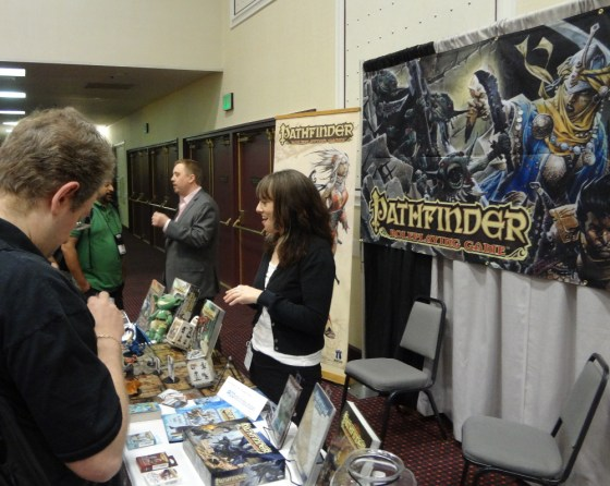 Pathfinder banner behind Jenny Bendel and Erik Mona at Paizo table in convention center