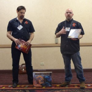 Arcane Wonders employees speak to press with Mage Wars boxes in hand