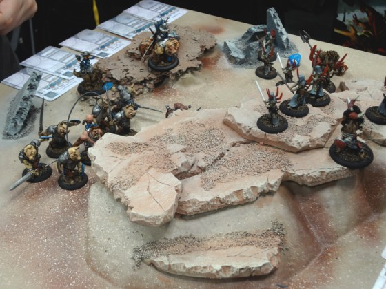 Piglike Teknes miniatures for Wrath of Kings battle against thin Nasier on desert demo board