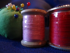 Spools of thread with Hugo's Amazing Tape wrapped around them keeping threads confined