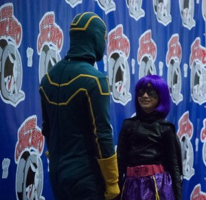 Kickass looks down at a grinning Hit Girl onstage at the Las Vegas Comic Expo's Cosplay Contest