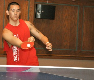 James De La Cerna, 19, sophomore of San Diego, chops the pingpong ball in one of the final heats of the tournament Sept. 16 in the Student Center. — Photo by Vera Ulitina