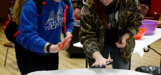 Shayleen Behm, left, 17, freshman of Alliance, and Brittany Fatlig, right, 20, junior of Elwood, try to find the perfect spot to put their hands on the sheet Monday night during the Beauty of Diversity event in the Gold Room. —Photo by Sara Tweet