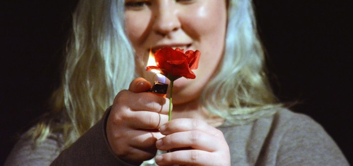 "Jennaya Hill, freshman of Gordon, sets a rose on fire Monday during play ""#16: Ten Years…and six months"" as part of a dress rehersal of ""Too Much Light Makes The Baby Go Blind,"" in the Black Box Theatre. —Photo by Jordyn Hulinsky"