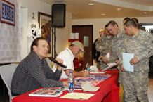 Pvt. Noe Sanchez leads the way for a group of Fort Carson Soldiers seeking hand-shakes and autographs from USO guests and Hall of Famers Rick Barry, left, and Goose Gossage.
