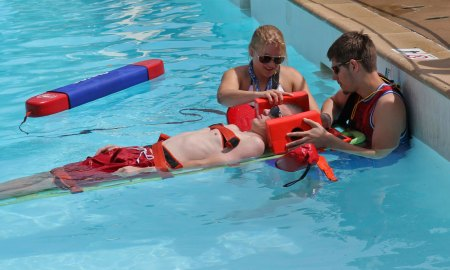 (Courtesy photo by Stephen Steinke) DENVER – Lifeguards from the Peterson Air Force Base Aquatic Center compete in the back boarding scenario portion of the 30th Annual Colorado Parks and Recreation Association Lifeguard Games at Water World, July 12, 2015. The team competed in the games to test their life-saving skills against other area lifeguards, placing in three out of six events.