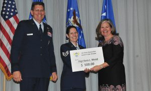 (Courtesy photo) PETERSON AIR FORCE BASE, Colo. ­— Staff Sgt. Kesa Wood, 16th Space Control Squadron NCO in charge of current operations at Peterson Air Force Base, Colo., receives a prize check from Kristen Christy, president of the Air Force Association Lance P. Sijan Chapter, and Maj. Gen. David Thompson, vice commander of Air Force Space Command, for being the 2016 Gen. Bernard A. Schriever Memorial Essay Contest winner for the Airman/NCO division.