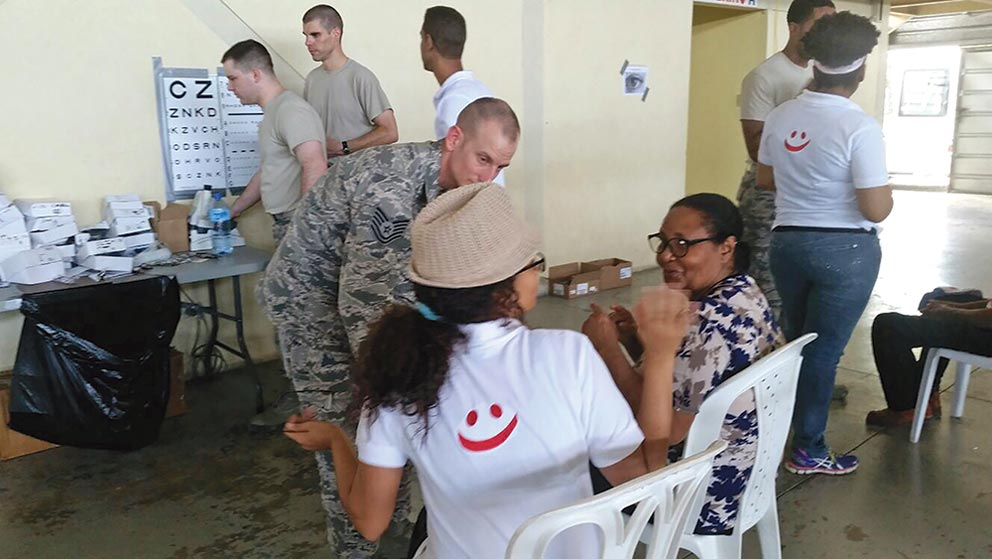 (Courtesy photo) Azua, Dominican Republic — Maj. Jeffrey Newsom, 21st Medical Group Optometry flight commander, right rear in sand T-shirt, and Senior Airman Todd Stout, 21st MDG optometry technician, left rear, assist patients in the optometry clinic in Azua, Dominican Republic during Operation New Horizons, an exercise run by Air Force South, March 3-18, 2017. A team from 21st Medical Group, Peterson Air Force Base, Colo., is leading the initial phase of the exercise for the first time since the operation began in 2008.