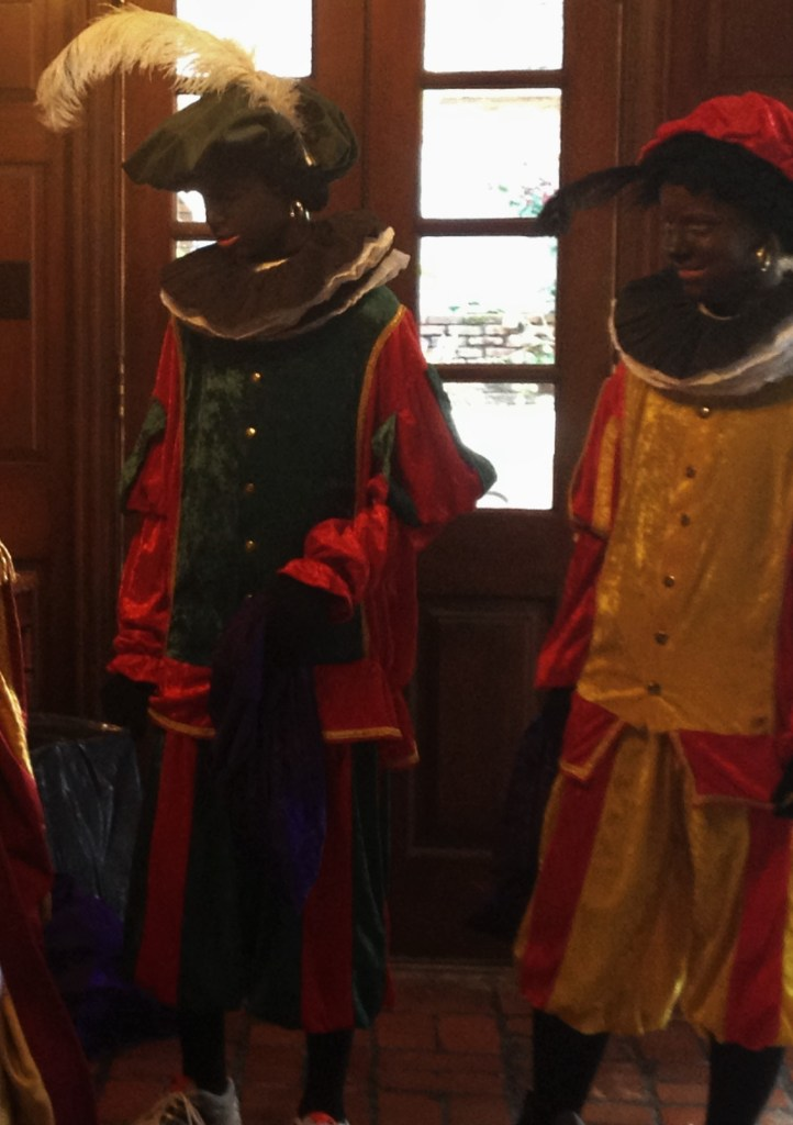 "Two Zwarte Pieten, or ""Black Peters"" smiling at Sinterklaas"