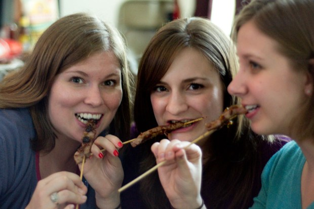 Girls eating orange beef on a stick