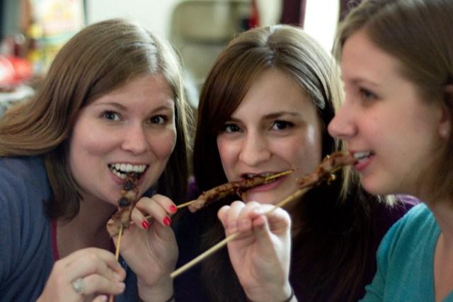 Girls eating orange beef on a stick