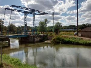 Pont levant sur le canal du nivernais avec un TER bourgogne en arrière-plan.