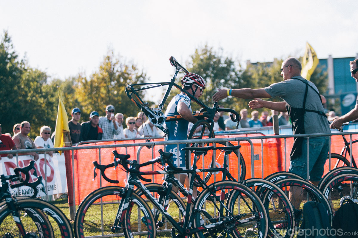 Jonathan Page walks back to the pits with his damaged bike after the start of of the first cyclocross World Cup race of the 2014/2015 season in Valkenburg.