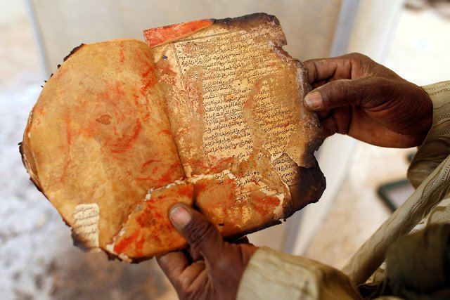 A museum guard displays a burnt ancient manuscript at the Ahmed Baba Institute in Timbuktu