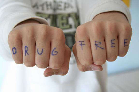 """Photo of a person's fists with the words """"drug free"""" written across the knuckles."""