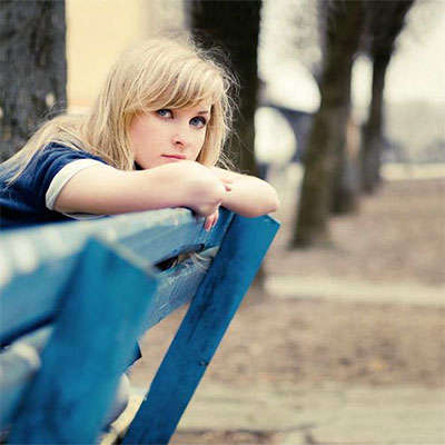 Photo of a young woman seated and leaning forward against the backrest of a park bench.