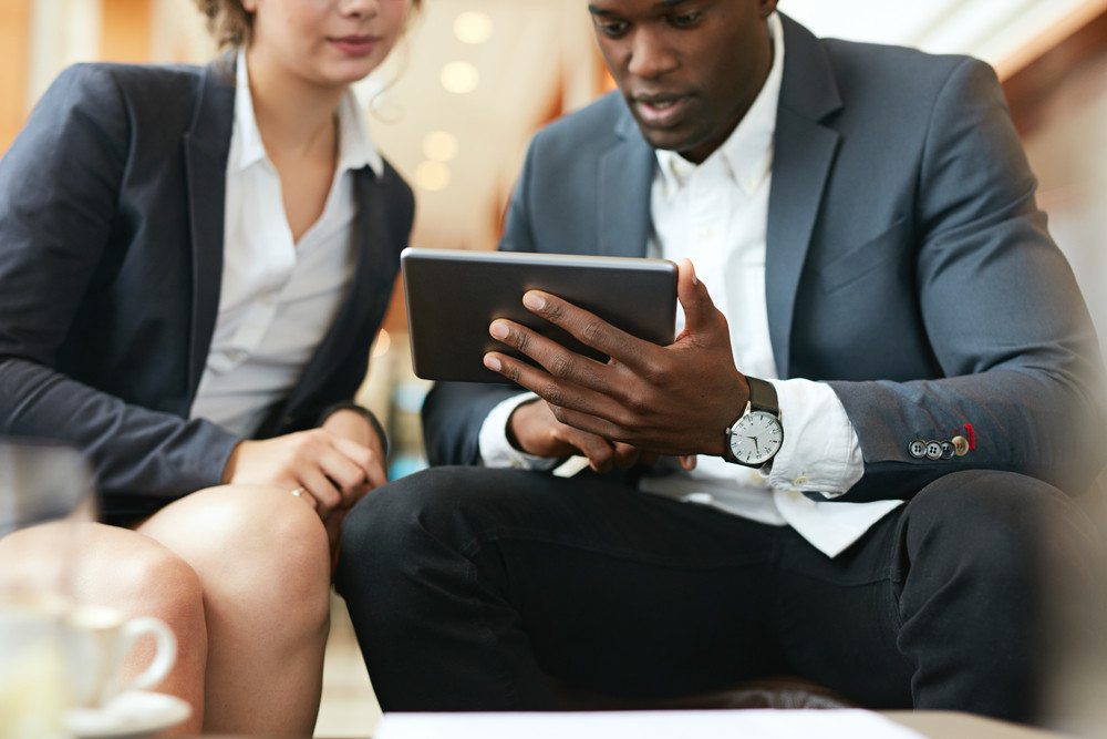 Close up shot of african business man showing something on digital - business tablet