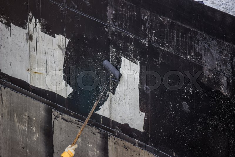 Waterproofing, worker painting exterior concrete wall with tar - Concrete Wall Insulation