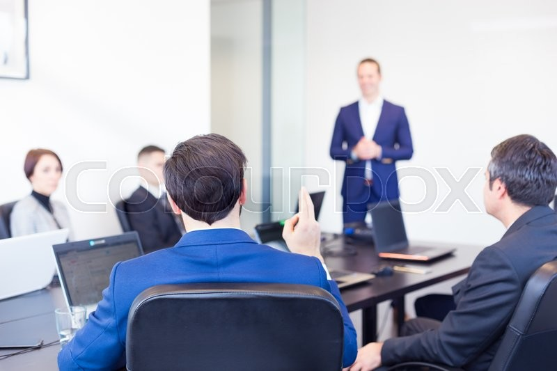 Colleague asking a question to businessman during a presentation