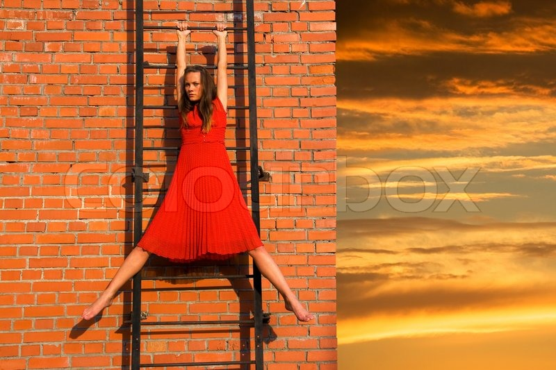 A Girl Hanging On The Fire Ladder Stock Photo Colourbox