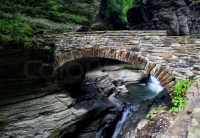 Stone bridge over stream with small waterfall | Stock ...