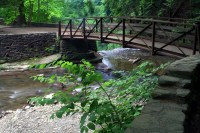 Wooden bridge over stream with small waterfall | Stock ...