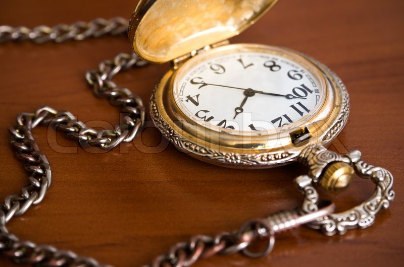 Old Retro Pocket Watch With Chain On Table Stock Photo