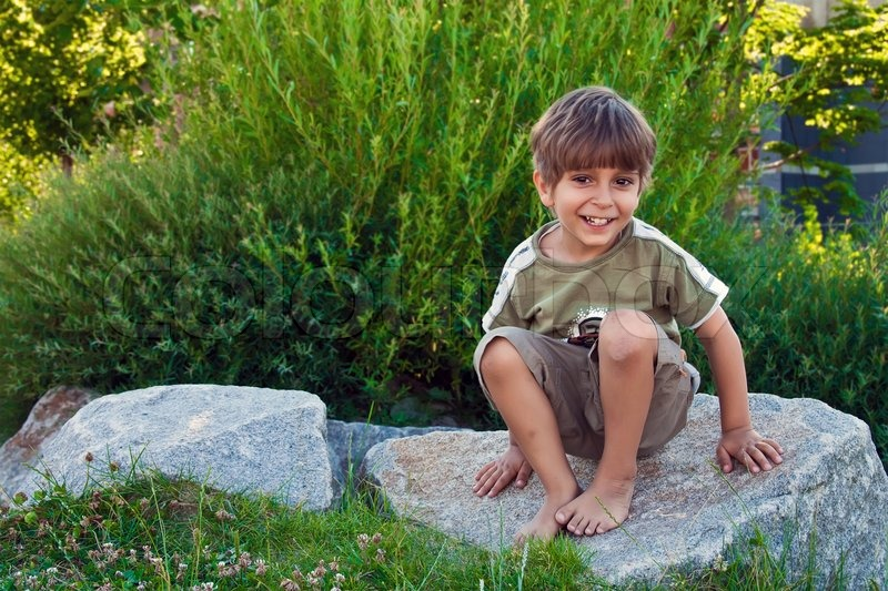 Girl And Boy Sitting On Bench Wallpaper Portrait Of A Young Boy Sitting On A Rock Stock Photo