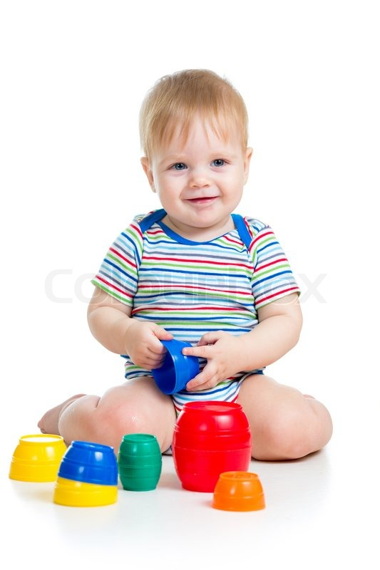 Cute baby boy playing with toys while sitting on floor, isolated