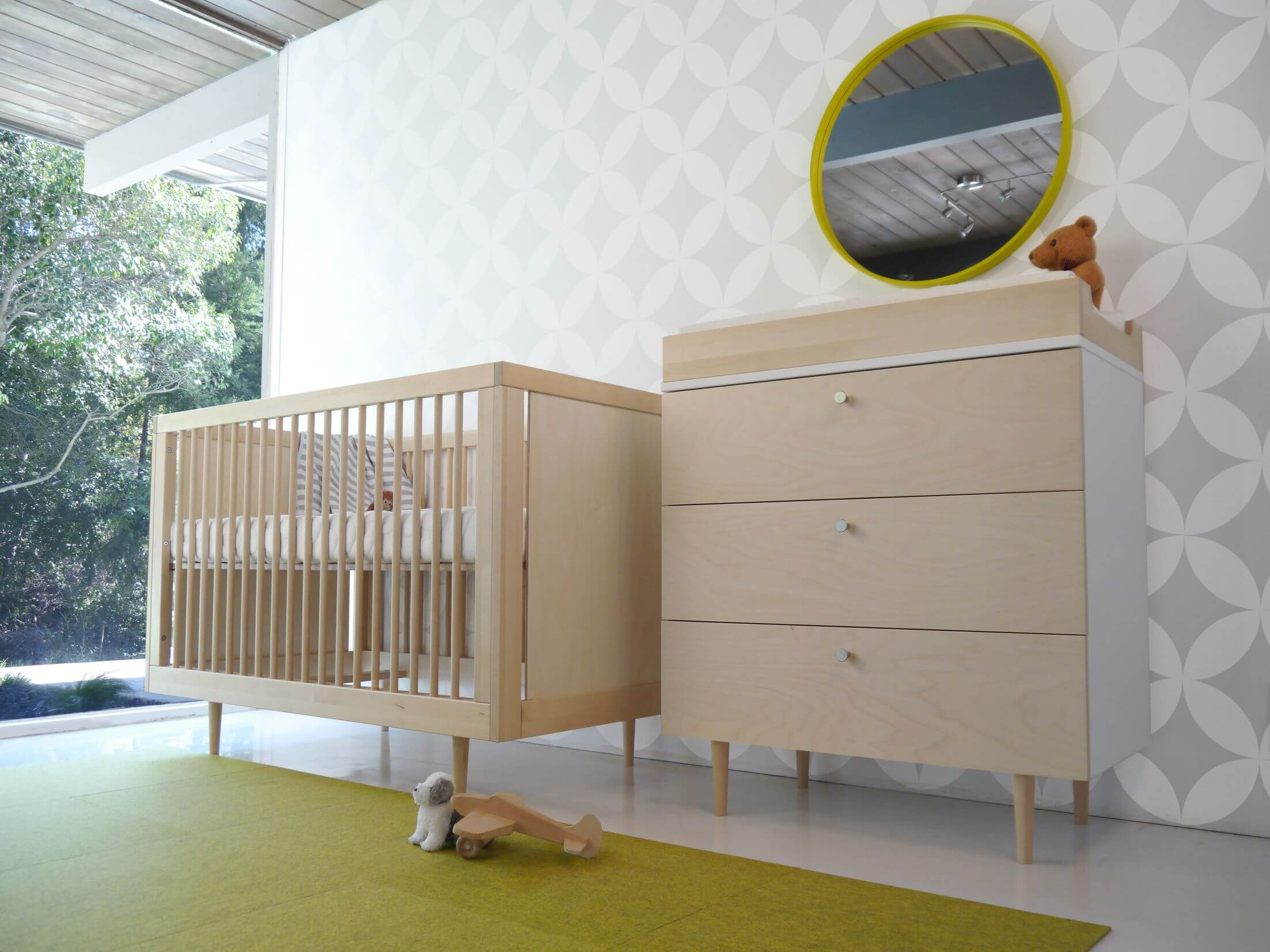 Light natural wood crib and matching changing table with dresser stand beneath patterned white and grey