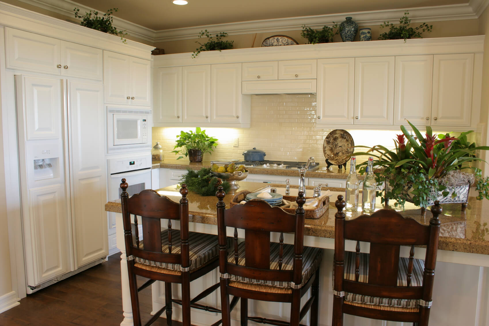 white kitchen designs pictures white kitchen dark floors White matte cabinetry paired with glossy white brick backsplash over brown marble countertops pulls this kitchen