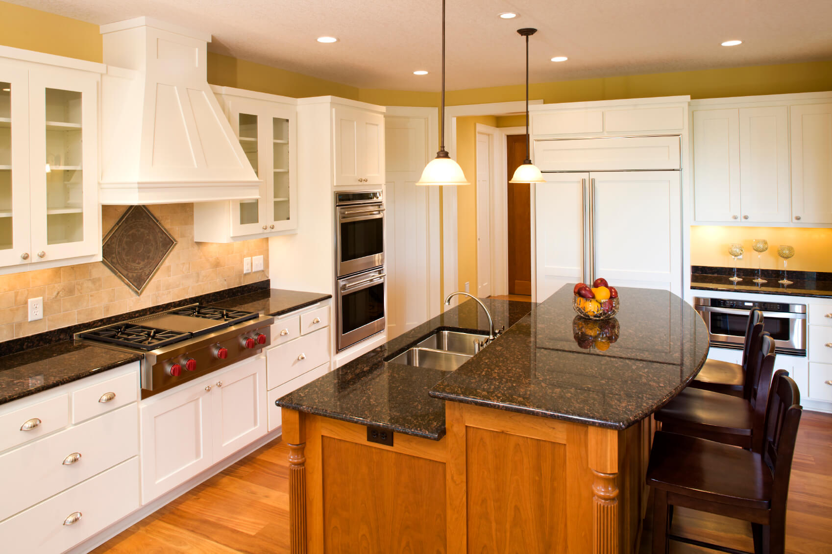 Here we have another two tiered island adding contrast to a kitchen with warm natural