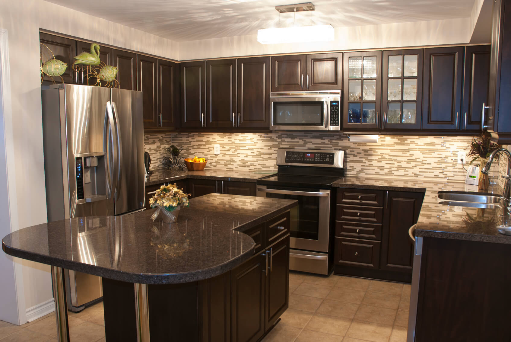 dark kitchen cabinets kitchen counters and backsplash Cozy kitchen is stuffed with dark wood cabinetry with brushed metal hardware Black marble
