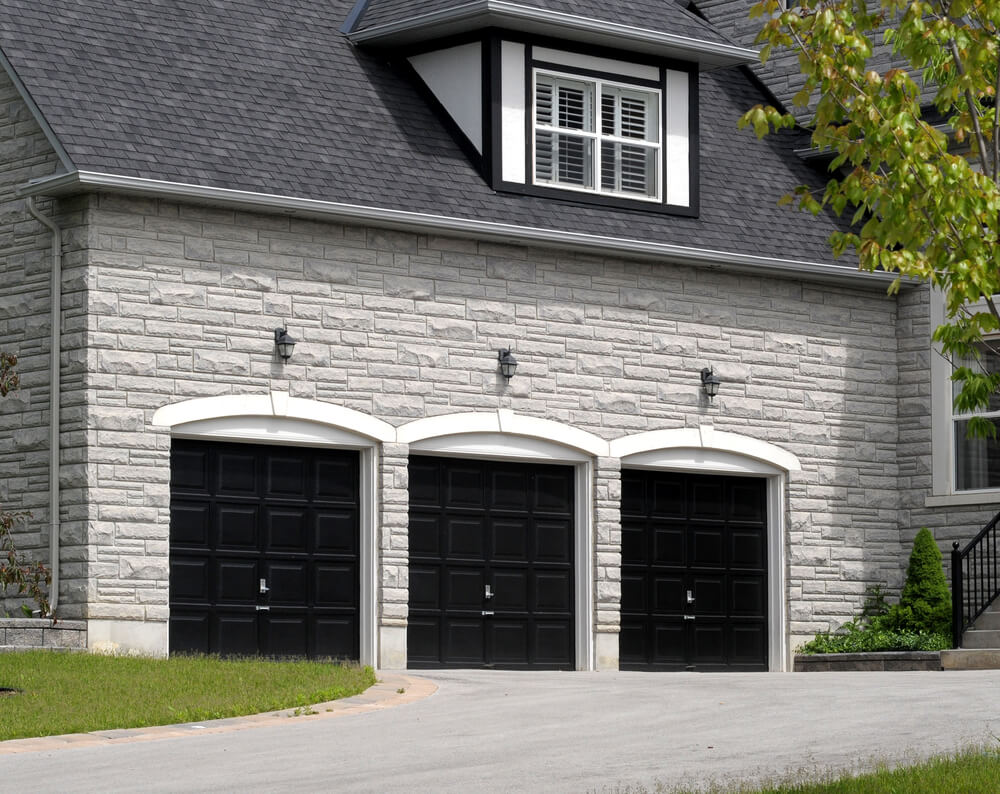 White stone brick home features three car garage with black door panels under arched stone