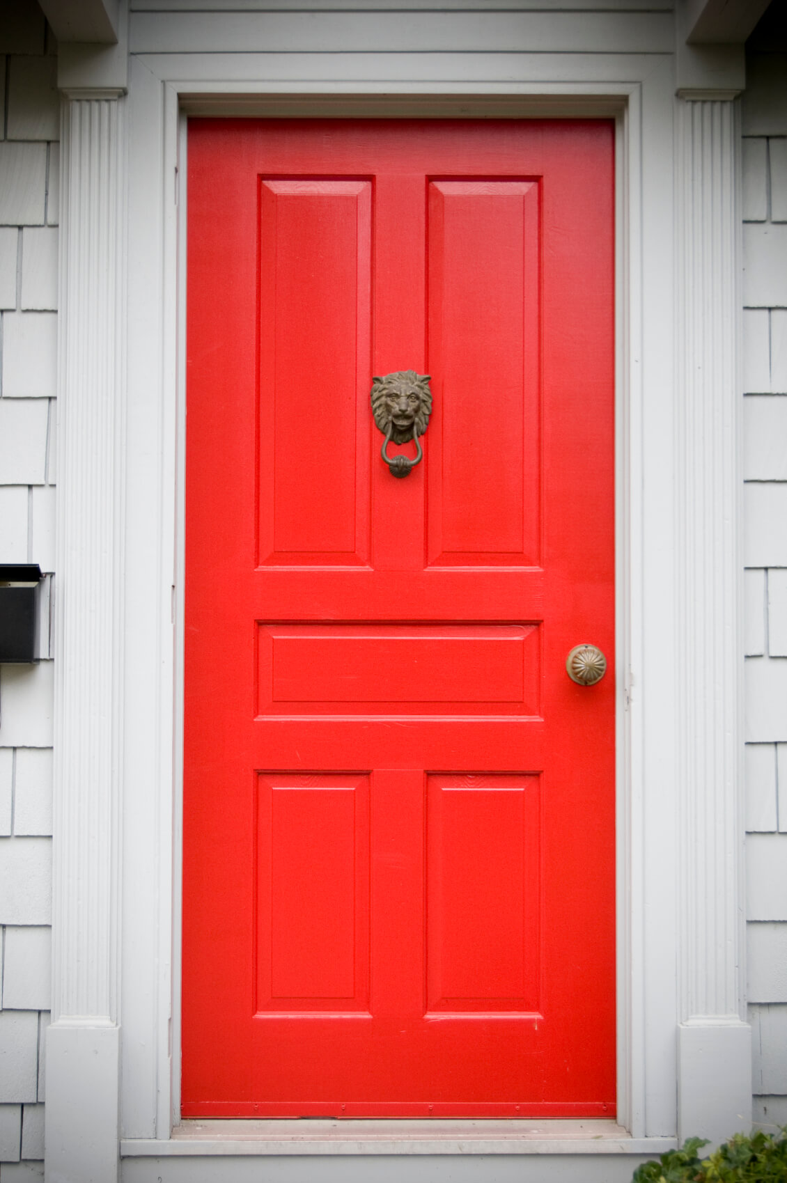 Off white molding and framing support this bright red door which has five rectangular