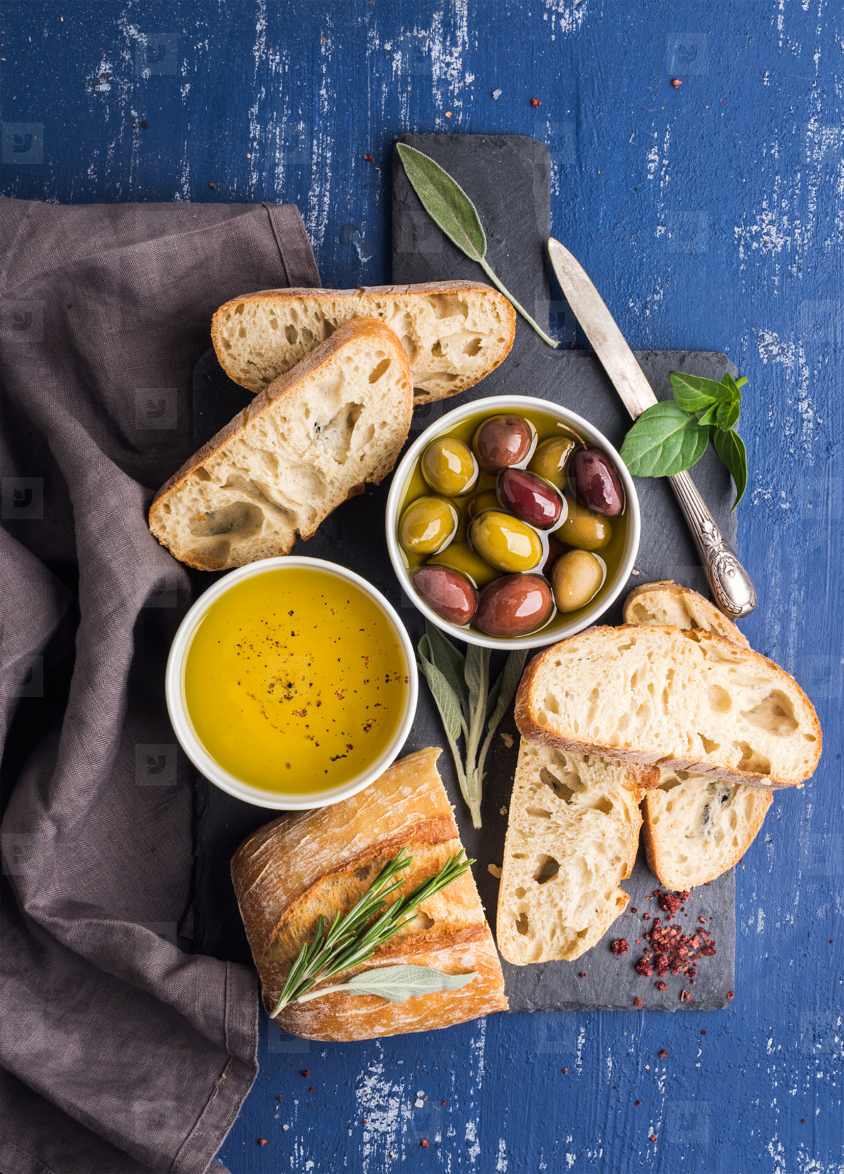 Mediterrane Küche An Bord Mediterranean Snacks Set Olives Oil Herbs And Sliced Ciabatta Bread On Black Slate Stone Board Over Painted Dark Blue Background