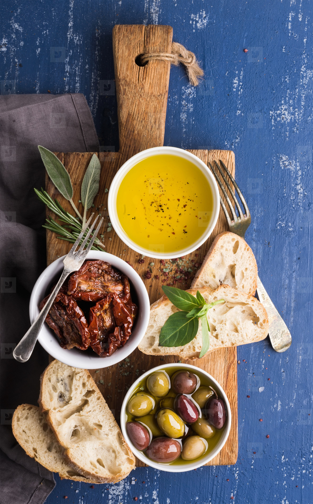 Mediterrane Küche An Bord Mediterranean Snacks Set Olives Oil Herbs And Sliced Ciabatta Bread On Yellow Rustic Oak Board Over Painted Dark Blue Background