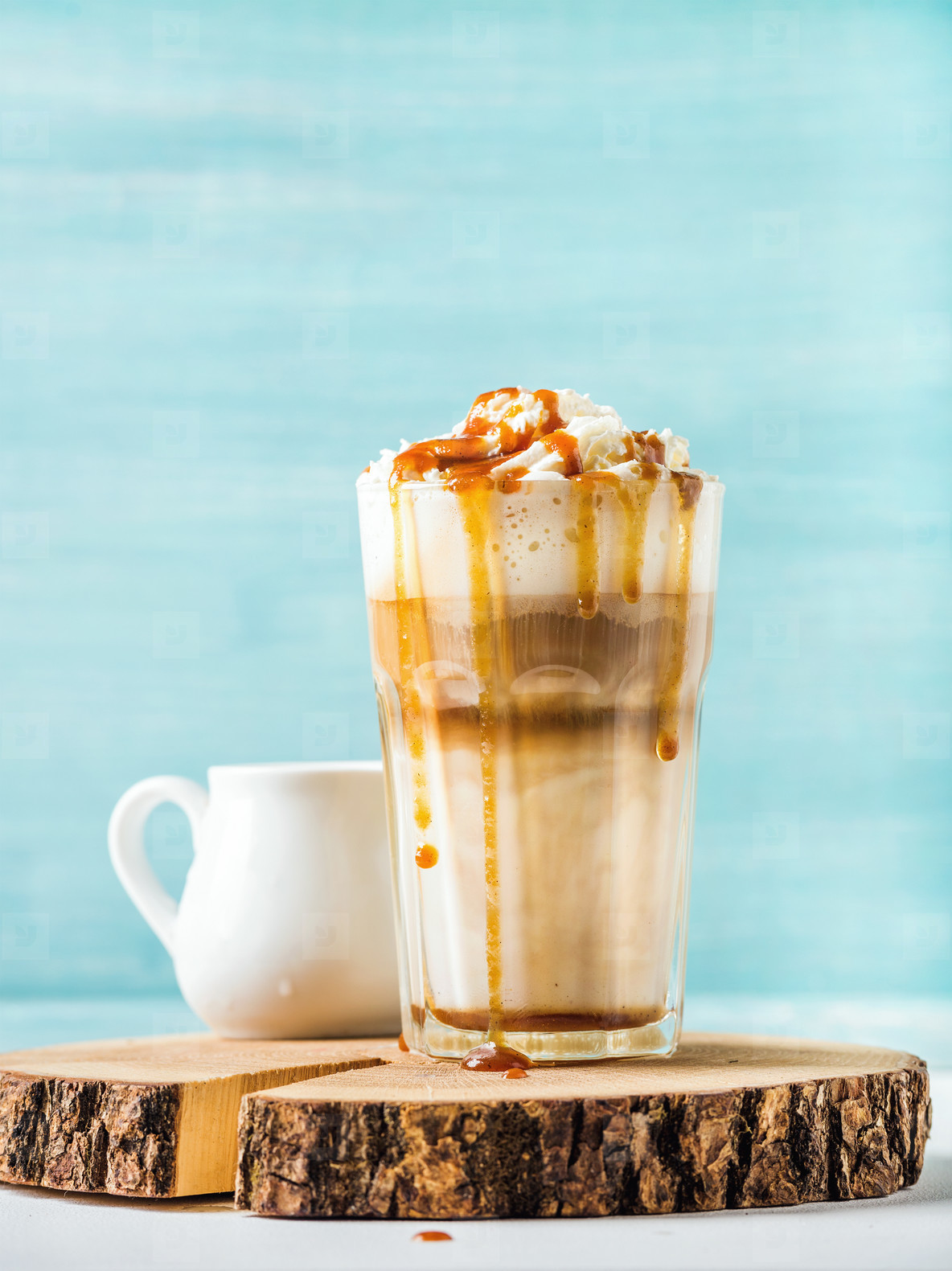 Macchiato Caramel Latte Macchiato With Whipped Cream And Caramel Sauce In Tall Glass On Round Wooden Serving Board Over Blue Painted Wall Background