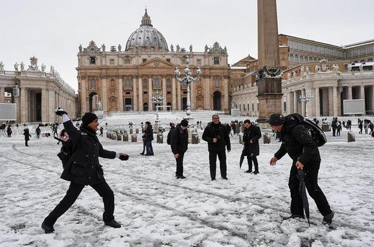 Turistas se lanzan bolas de nieve en la Plaza de San Pedro en el Vaticano, en una muy inusual imagen. (Foto Prensa Libre: EFE)
