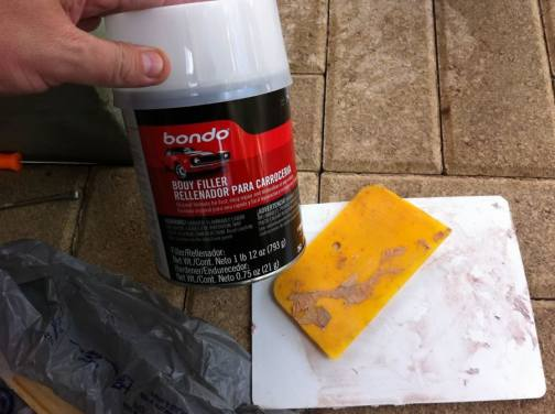 This is the Bondo Body Filler.  (Lowe's P/N 40188: http://www.lowes.com/pd_40188-98-262_0__?productId=3274225) Good auto body shops use very little of it to fill dents. Bad body shops build quarter panels from it. But this is a door on your house. So just mix it up like the can says and spread it over the dent.  Use some Bondo Spreaders. (Lowe's P/N 186730: http://www.lowes.com/pd_186730-98-30357_0__?productId=3961615) If it's hot out, it will harden up pretty quick. So work fast.