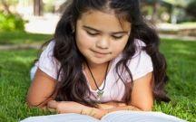 Hispanic girl laying in grass reading book