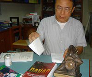 Macario Tiu in his Ateneo office. Before him is a copy of his book and the National Book Award trophy (davaotoday.com photo by Tyrone Velez)